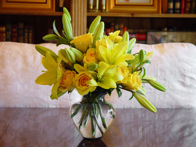 Monochromatic yellow dining room arrangement of lilies and roses