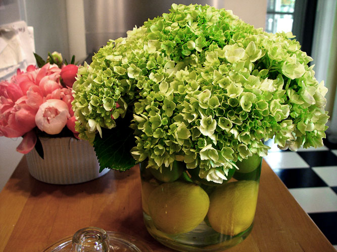 Summer arrangement of hydrangeas and lemons.