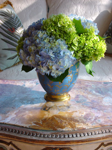 Elegant arrangement of green and blue hydrangeas in a gold porcelain William Yeoward container.