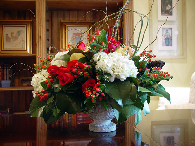 Christmas centerpiece designed with magnolia, berries, hydrangeas, roses, and curly willow.