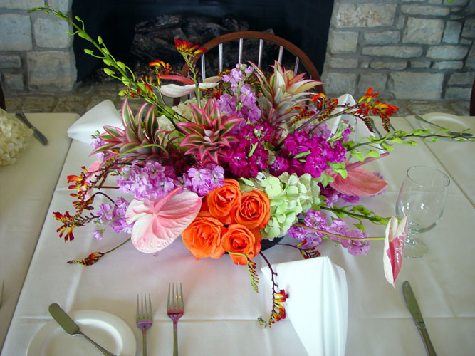 Exotic centerpiece of orchids, crocosmia, anthurium, proteas, and pineapple roses