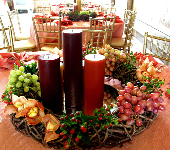 Lush fall wedding centerpiece for wedding at a winery filled with orchids, berries and grapes.