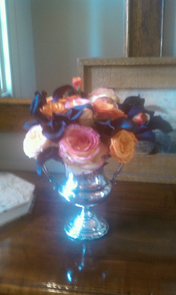 Arrangement of plum calla lilies and garden roses in sterling silver