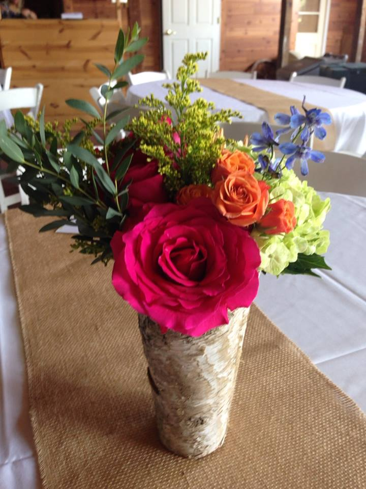 Setting up centerpieces in a barn for a wedding